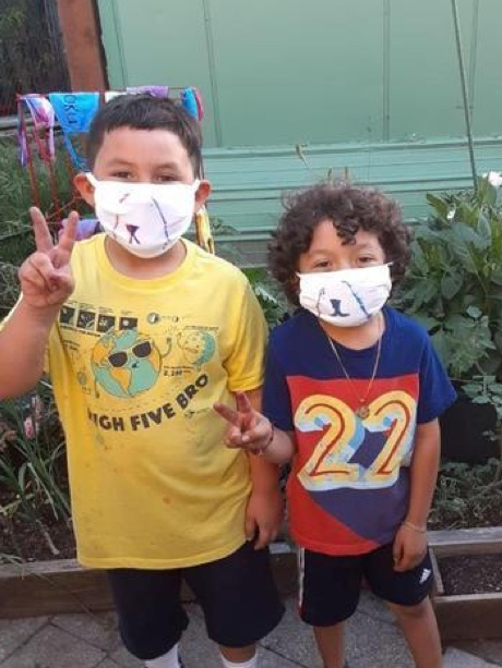Two young children wearing masks making the peace sign