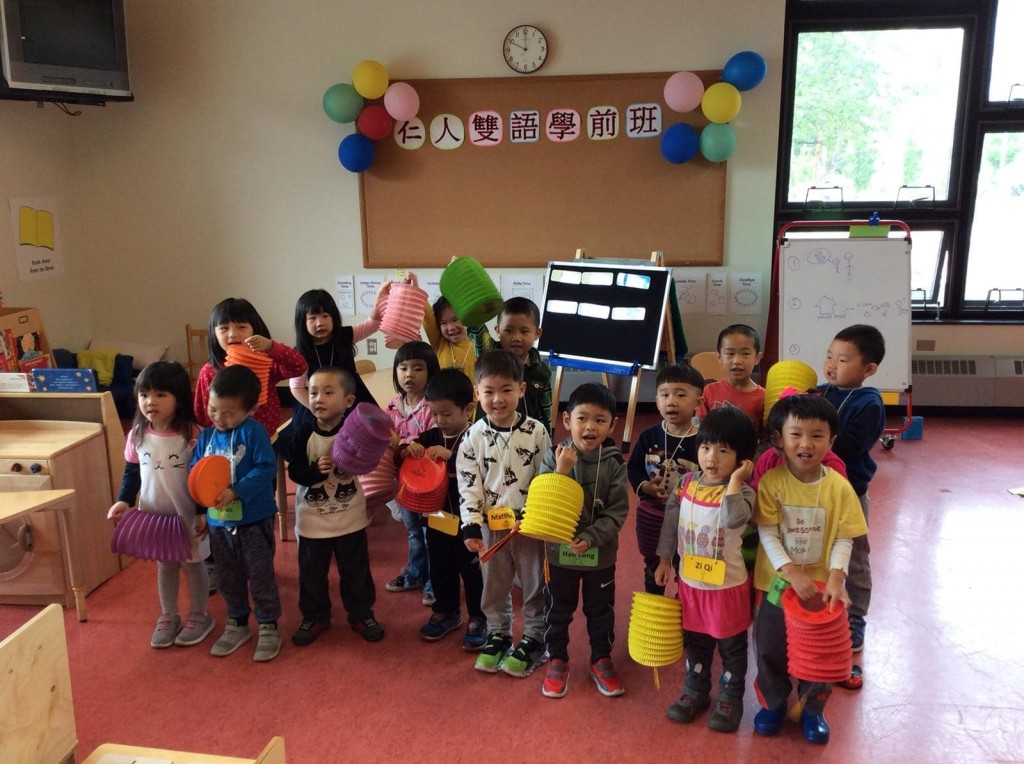 A group of children hold paper lanterns.